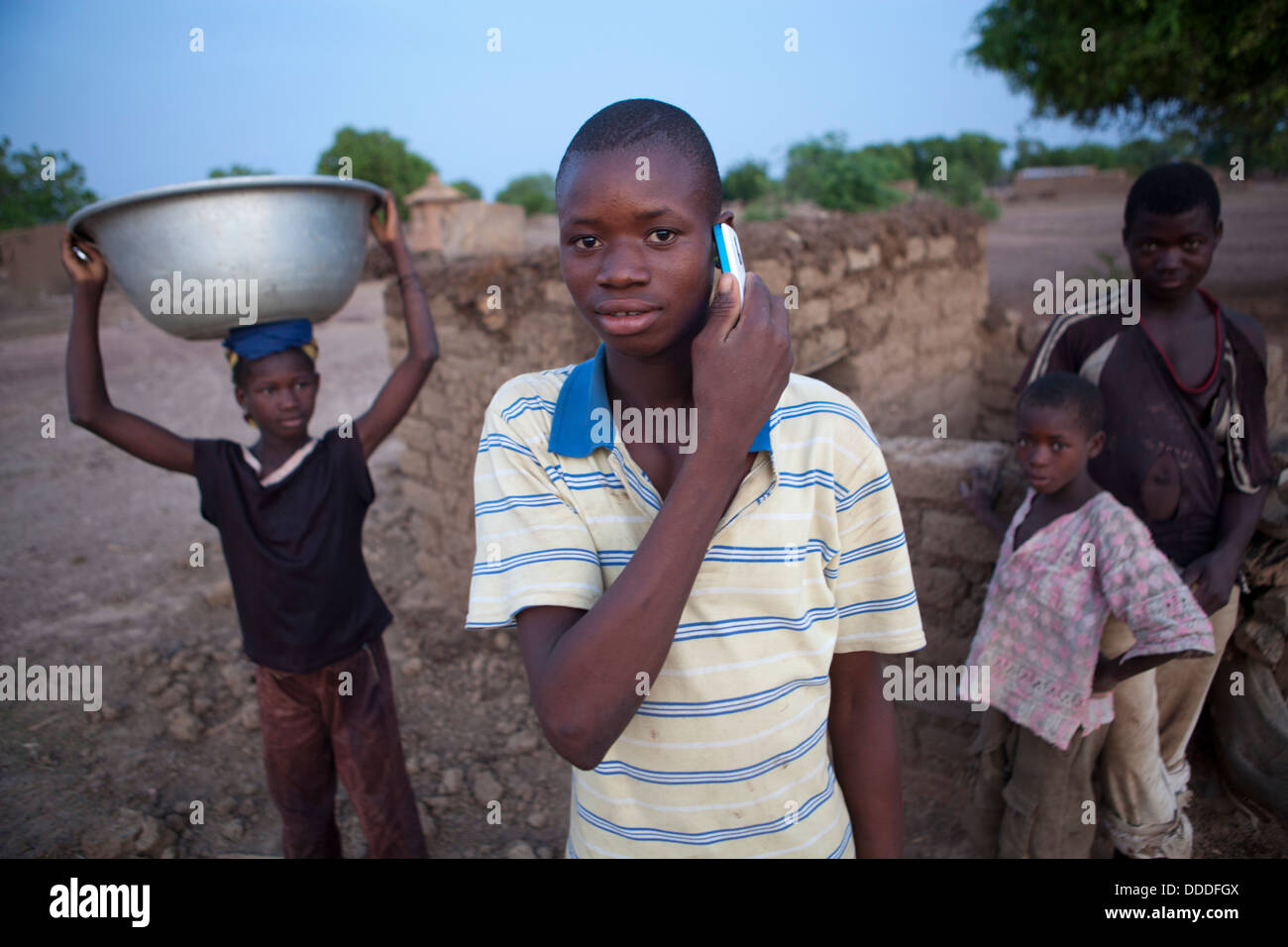Talking on a mobile phone in rural Burkina Faso. - Stock Image