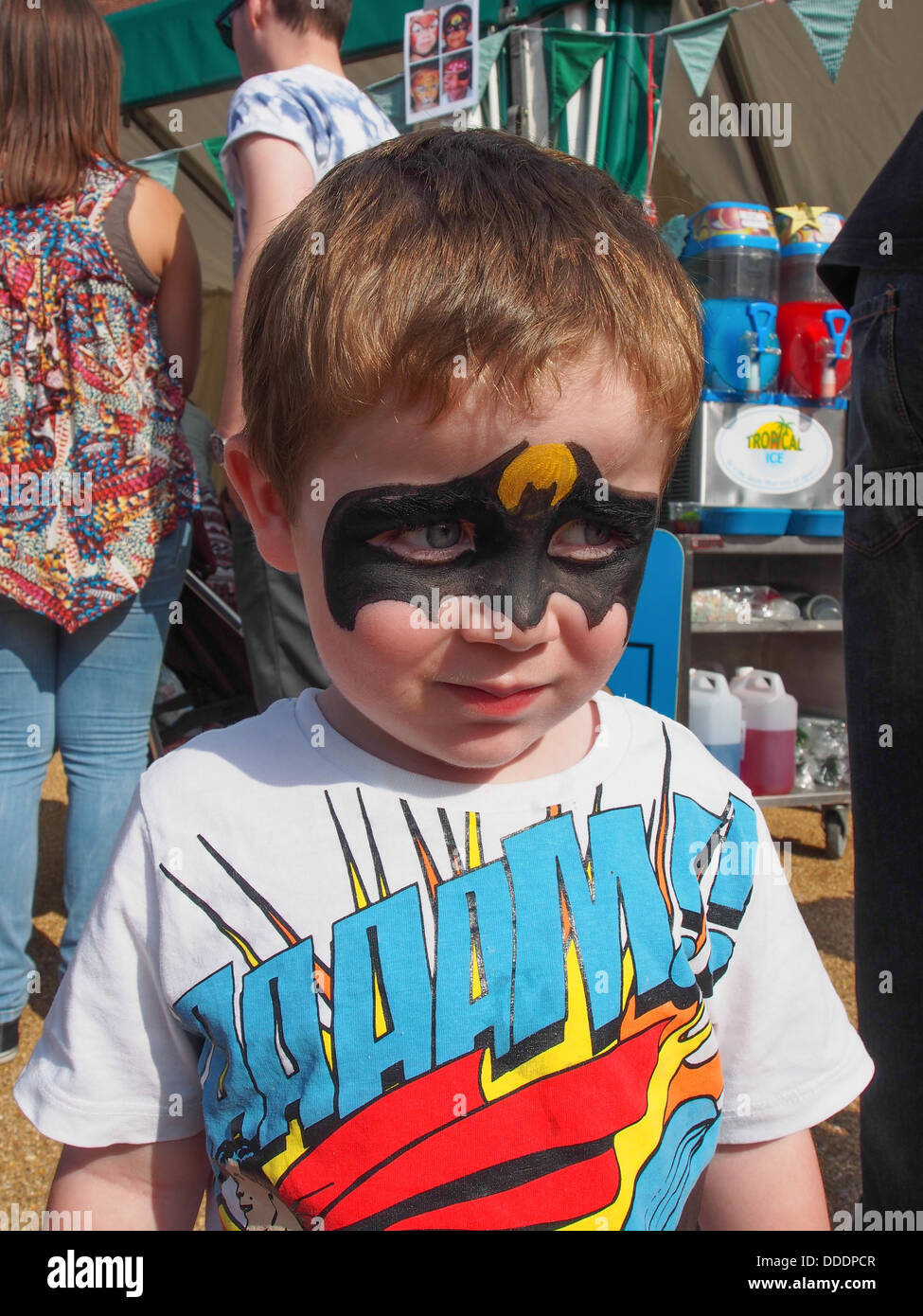 Young boy with superhero face paint at a summer festival - Stock Image