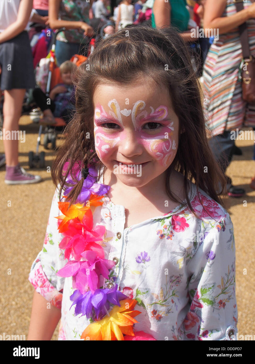 Young girl with her face painted and wearing a garland of flowers at a summer festival - Stock Image