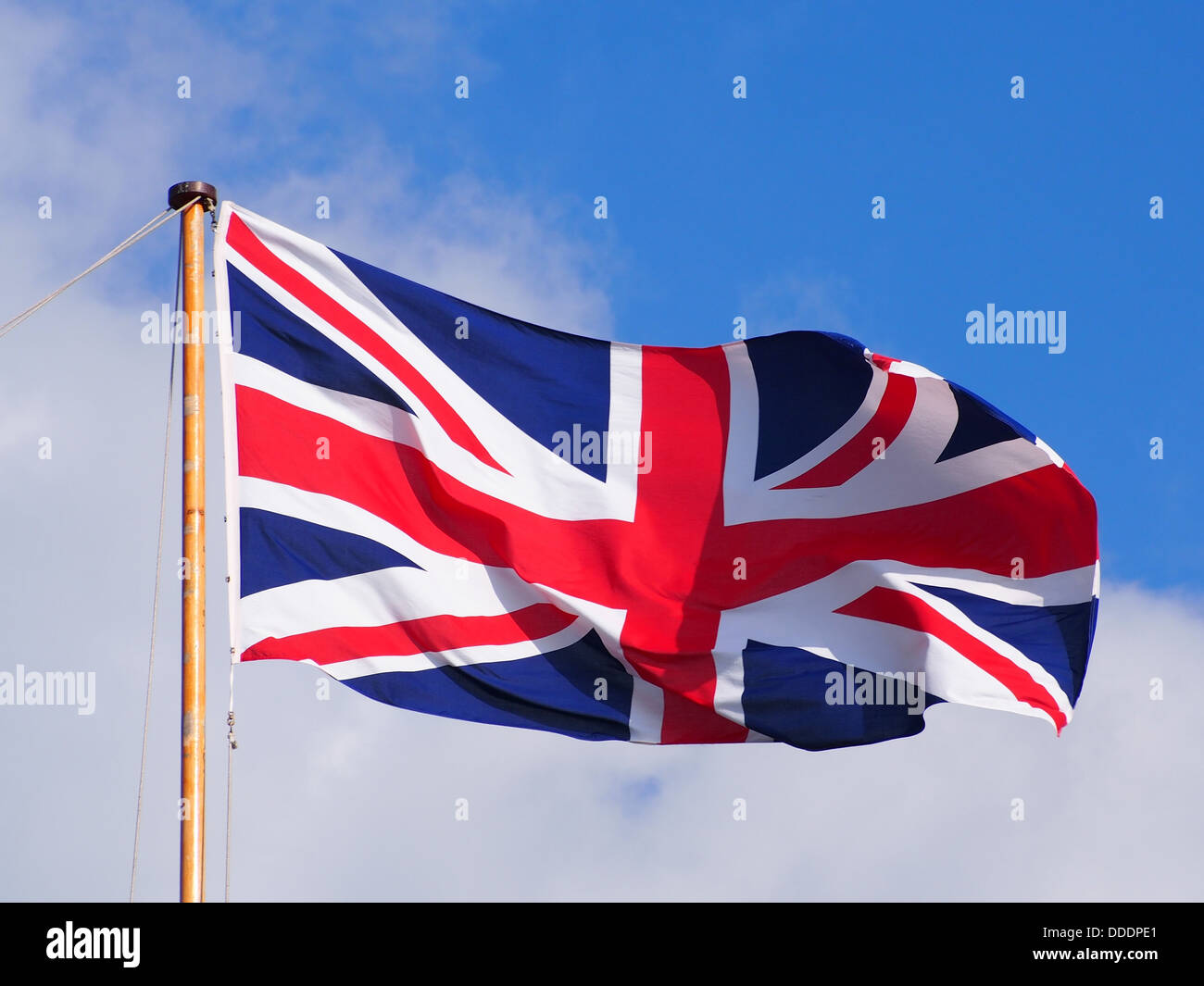A Union Flag flying at the top of a flagpole against a partly cloudy blue sky - Stock Image
