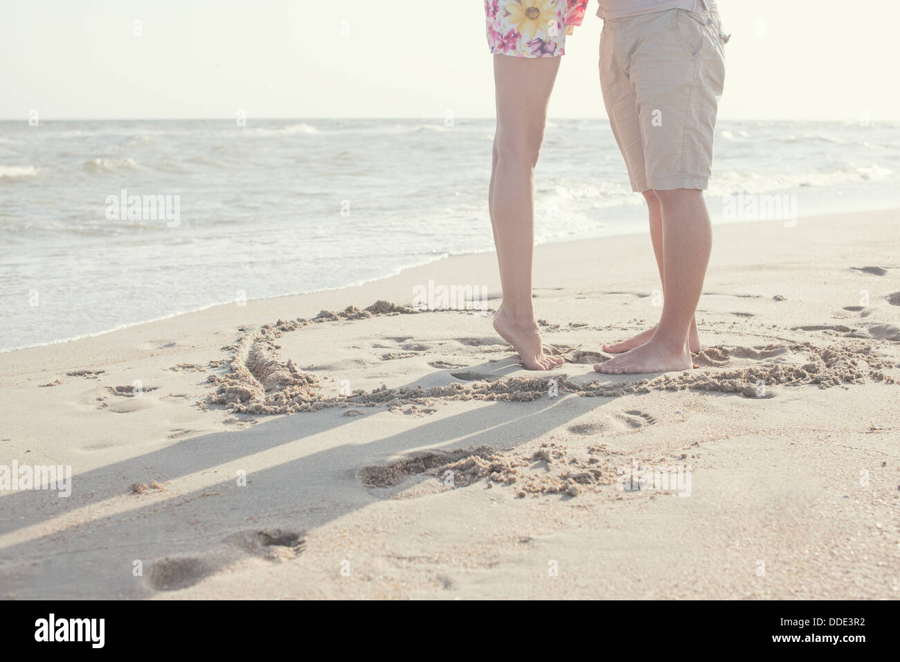 Couple legs standing inside heart picture on the sand. Summertime fun - Stock Image