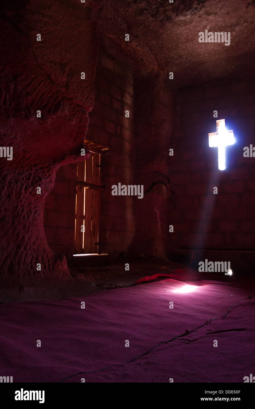 Light from a cross-shaped window shines on the red carpet of a rock cut church in Lalibela, Ethiopia - Stock Image