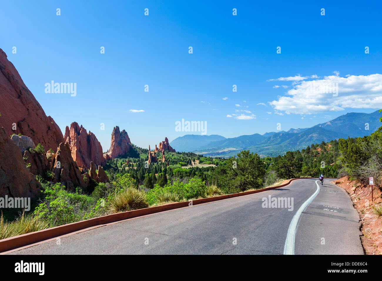 Road through Garden of The Gods public park with two cyclists in the distance, Colorado Springs, Colorado, USA - Stock Image