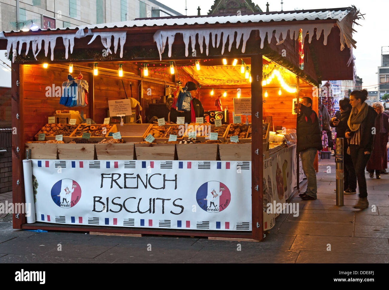 Customers browsing a Le Mareski Team French Biscuits stall at the Christmas Market, St Enoch Square, Glasgow - Stock Image