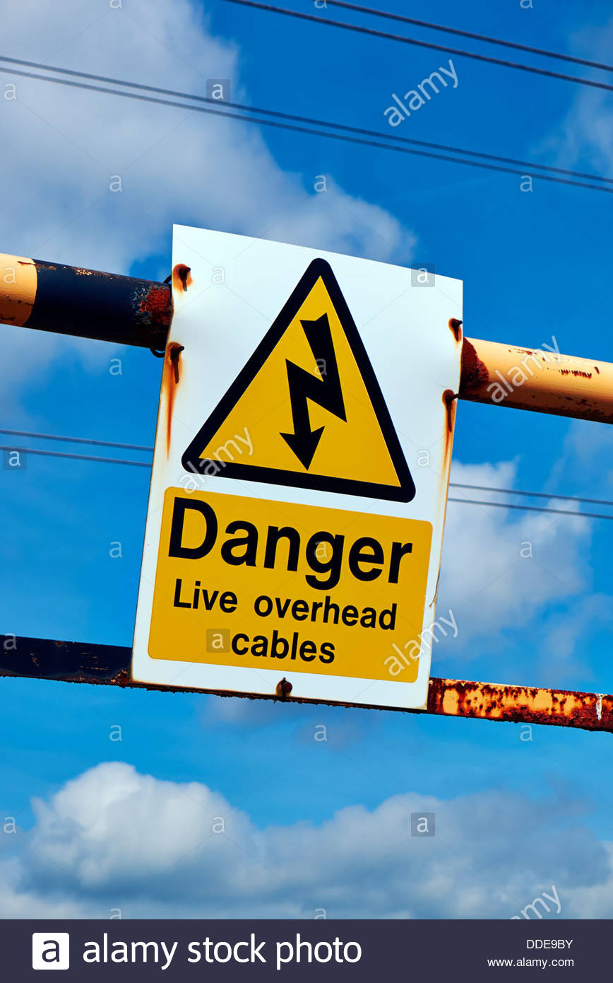 yellow black warning danger sign for live overhead electrical cables against blue sky - Stock Image
