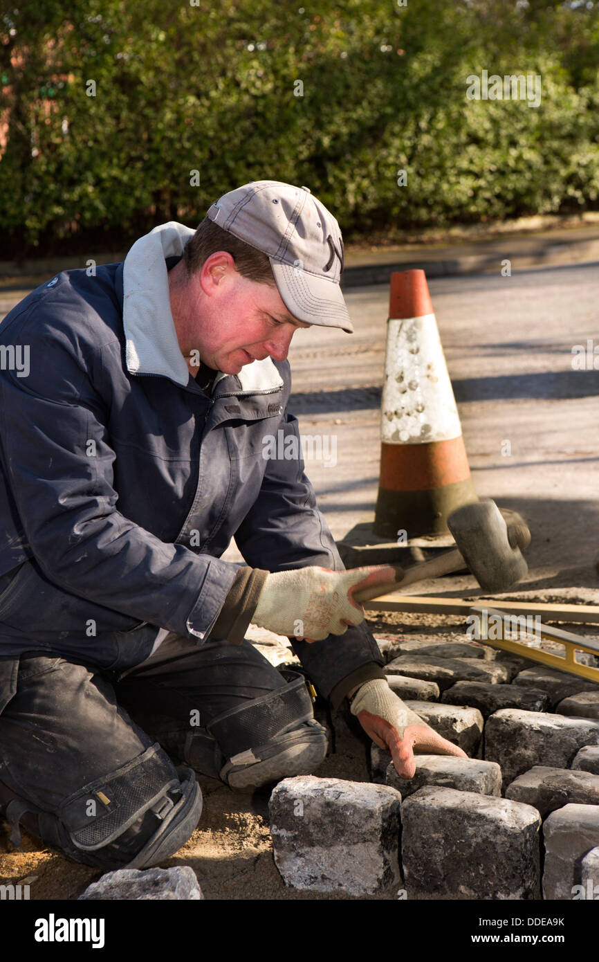self building house, hard landscaping, workman laying reclaimed granite setts at entrance to driveway - Stock Image