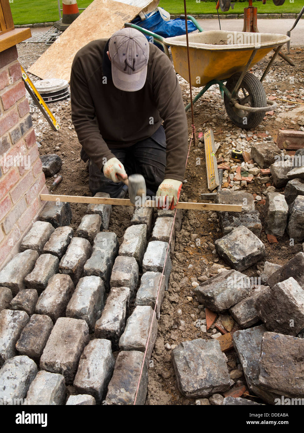 self building house, hard landscaping, workman laying reclaimed granite setts around new build home Stock Photo