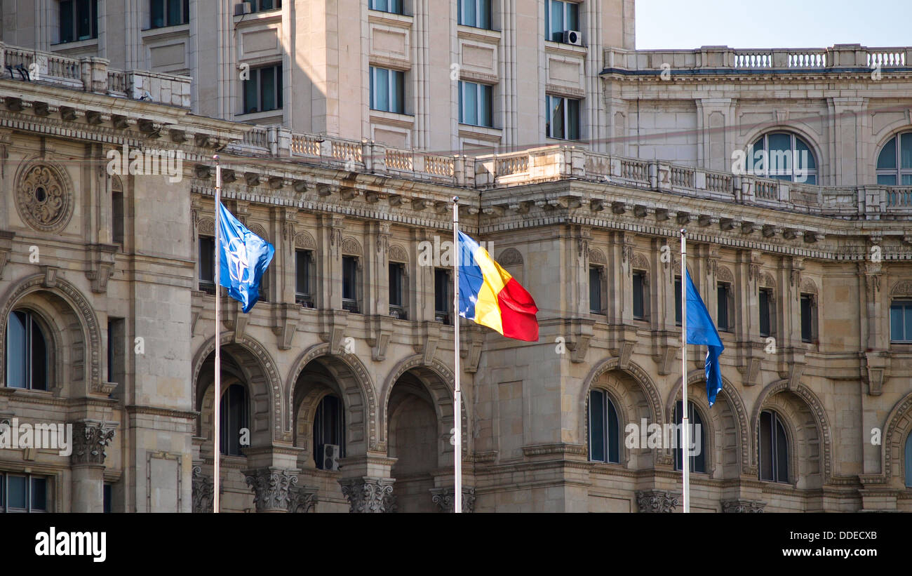 Romanian flag, along with NATO and European Union flags, in front of the Palace of Parliament. - Stock Image