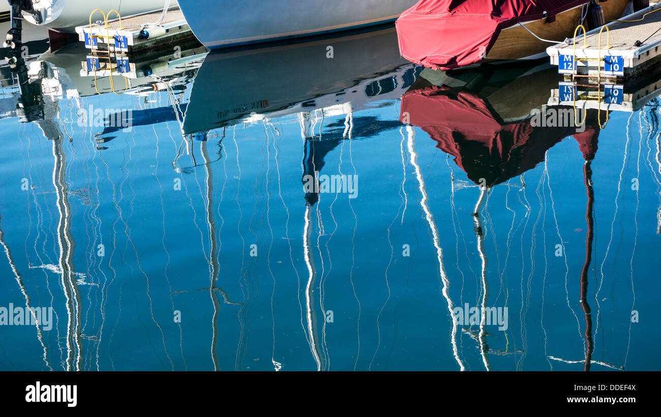 moored sailboats blend with beautiful watery images of boat hulls & wavering masts against blue sky Edmonds - Stock Image