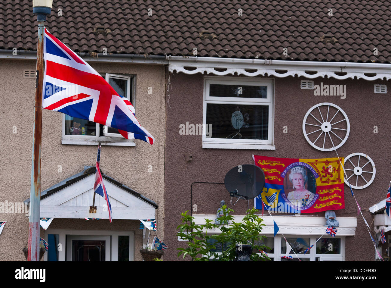 A Union Jack flag flies from a house on a housing estate in Protestant west Belfast in Northern Ireland - Stock Image