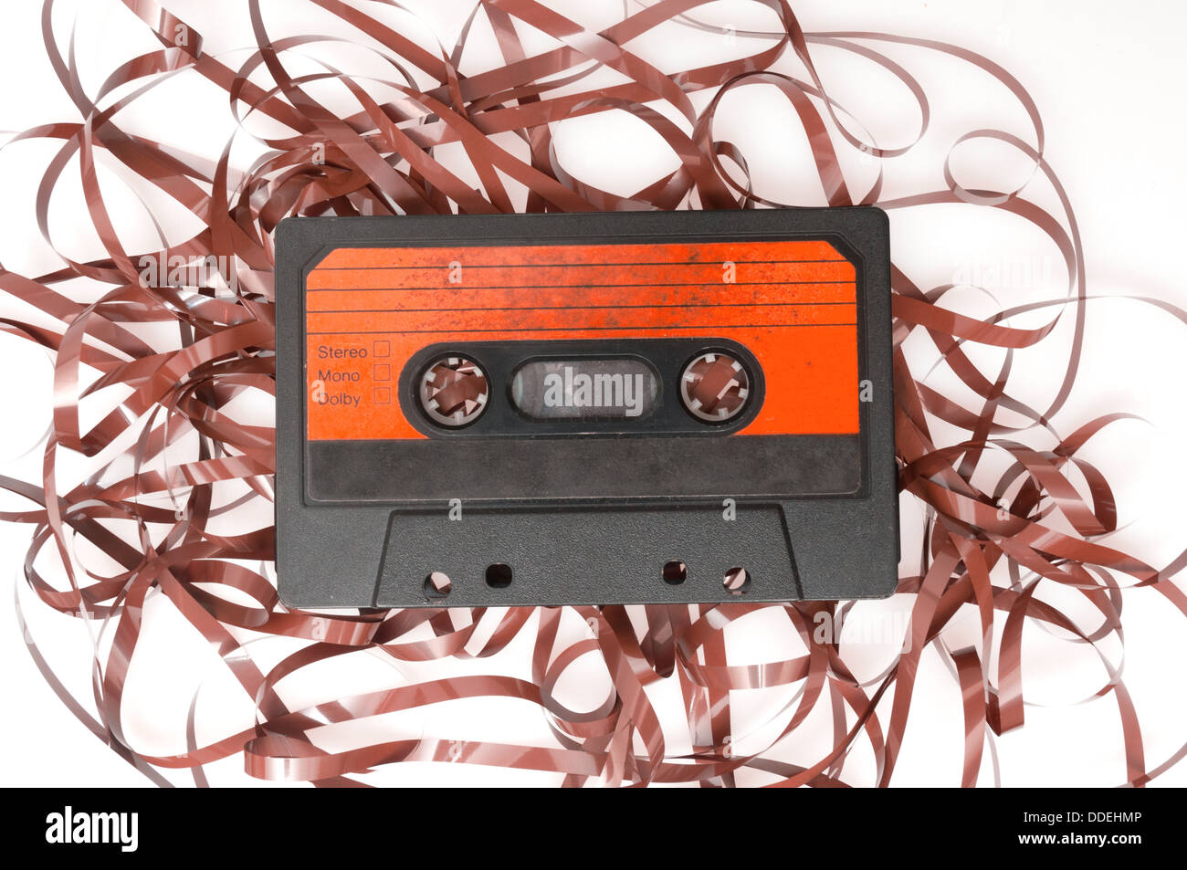 Retro Audio Cassette Tape With Pulled Out Tape on White Background - Stock Image
