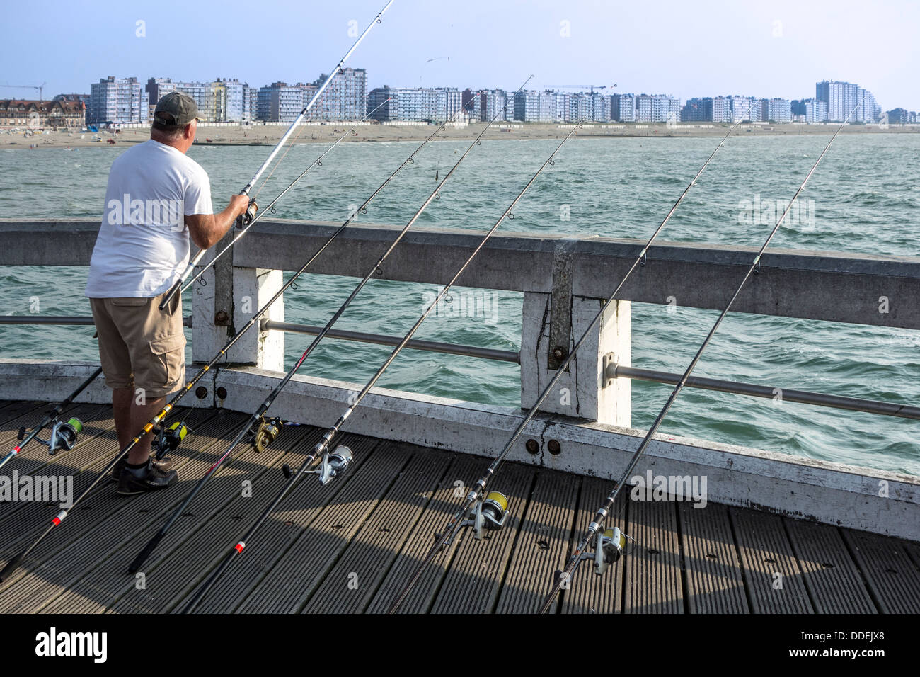 Angler fishing with several fishing rods from pier along the North Sea coast at Nieuwpoort / Nieuport, Belgium - Stock Image