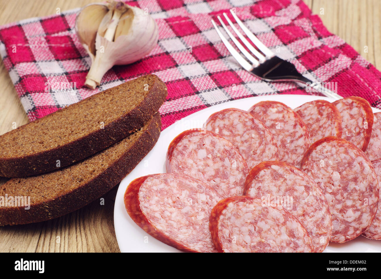 Smoked sausage sliced and bread on wooden table Stock Photo