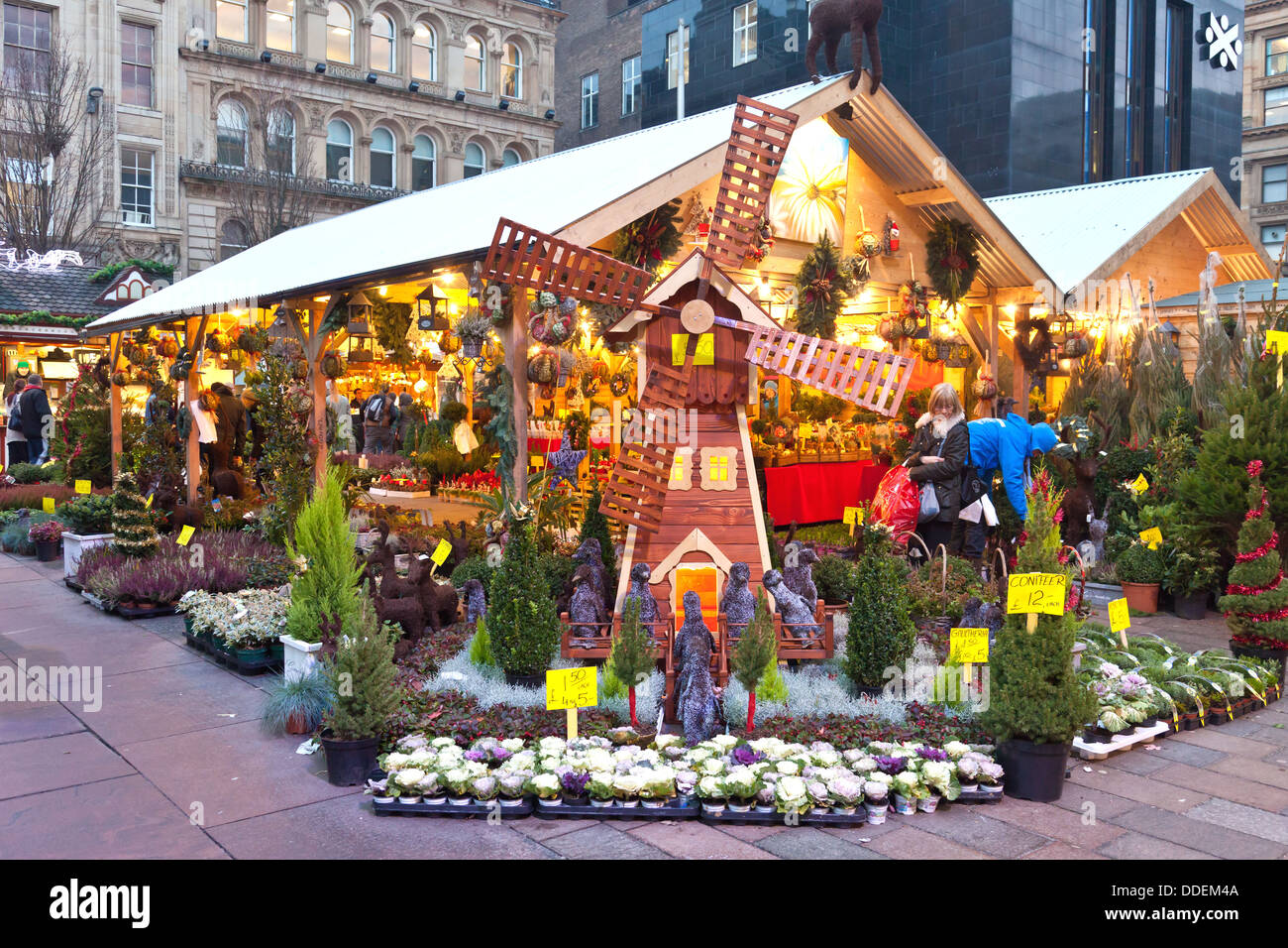 Customers browsing a stall selling potted conifers, wreaths and decorations at the Christmas Market, St Enoch Square, - Stock Image
