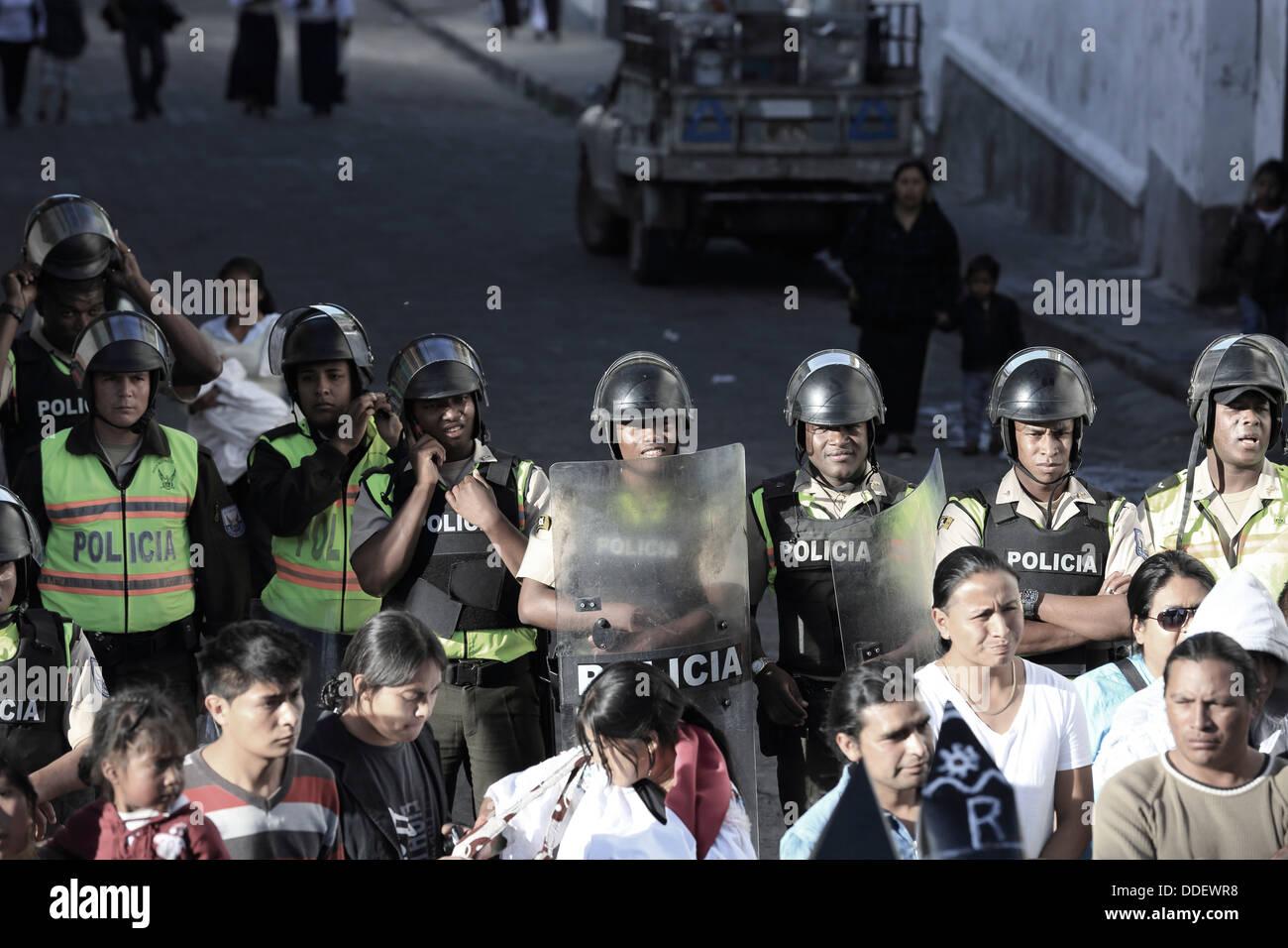 Riot police watch proceedings during Inti Raymi festivities in Cotacachi, Ecuador - Stock Image