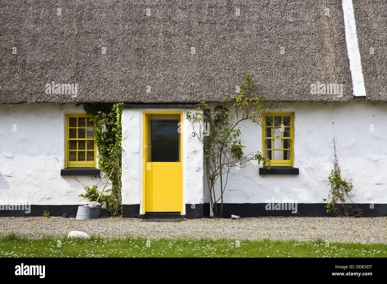 Picturesque thatched cottage with yellow door and windows in Ballyvaughan, Ireland, Europe - Stock Image