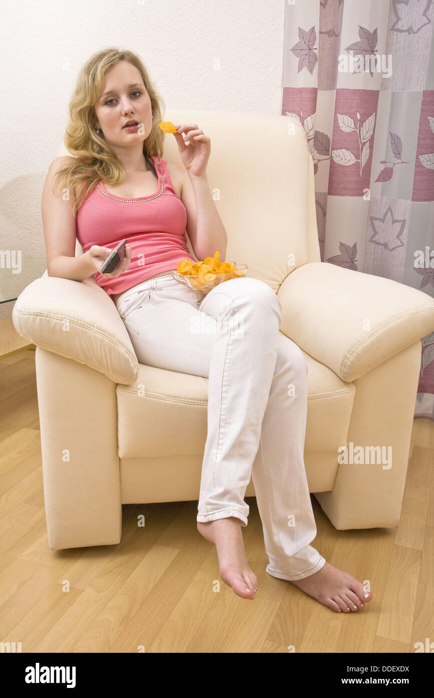 Young woman zapping and eating chips - Stock Image