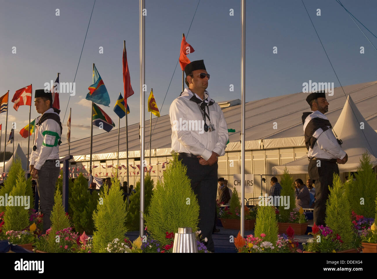 Muslims standing amidst national flags as a mark of respect to host country (UK) and the community during Jalsa - Stock Image