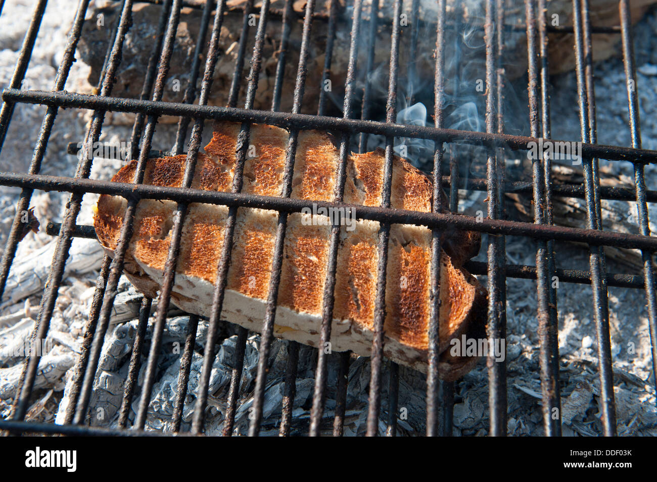 Slice of bread toasted on a campfire, Kunene River, Namibia - Stock Image