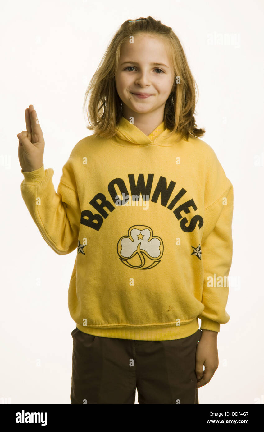 10 year old girl dressed in her Brownies uniform giving the three fingered salute - Stock Image