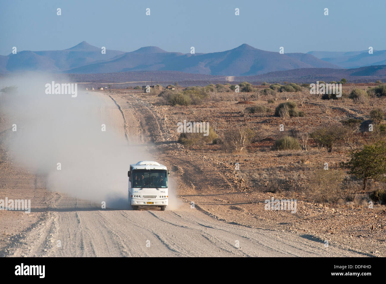 Tourist bus driving in a cloud of dust on a wide, dusty gravel road, Kunene Region, Namibia - Stock Image