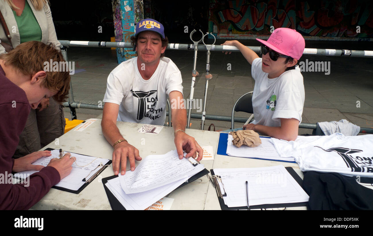 A man signs a petition supporting the campaign to save the Southbank South Bank undercroft skateboarding park London - Stock Image