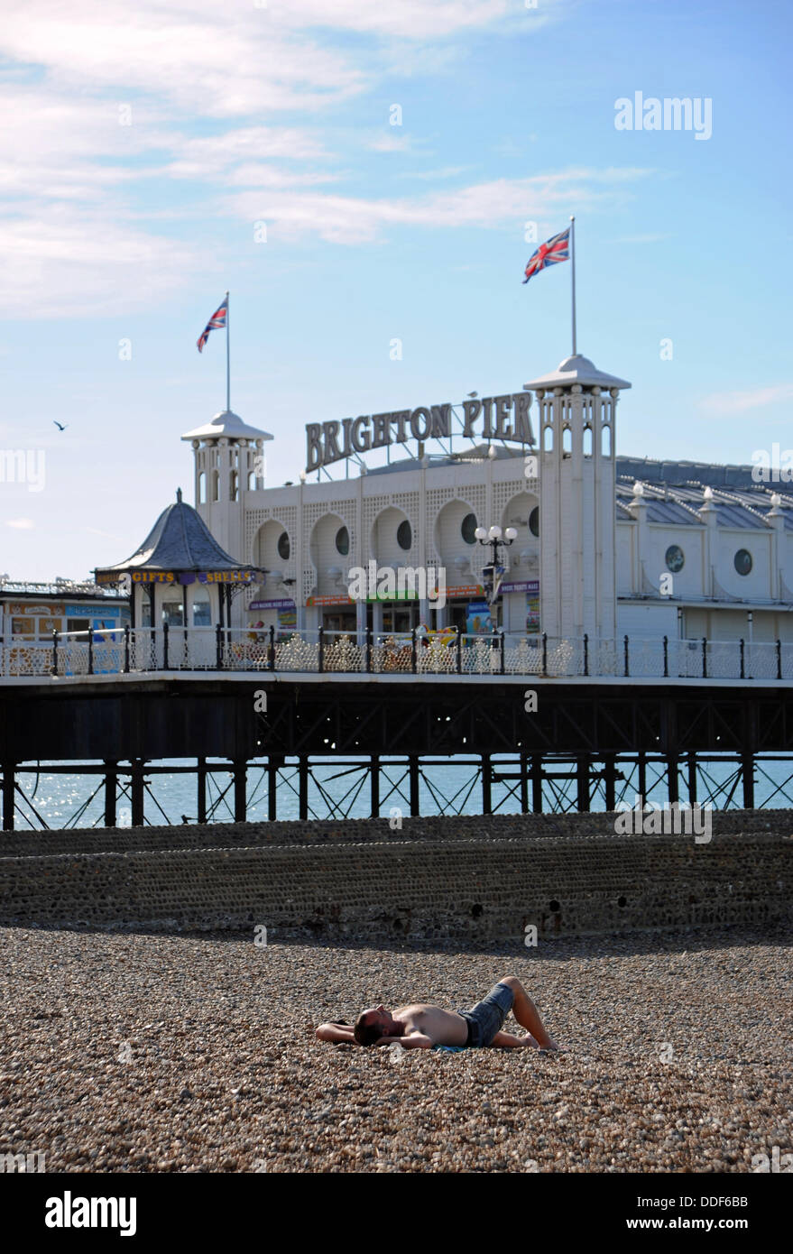 Brighton UK 2 September 2013 - An early morning sunbather on Brighton beach by the pier today as the hot summer - Stock Image