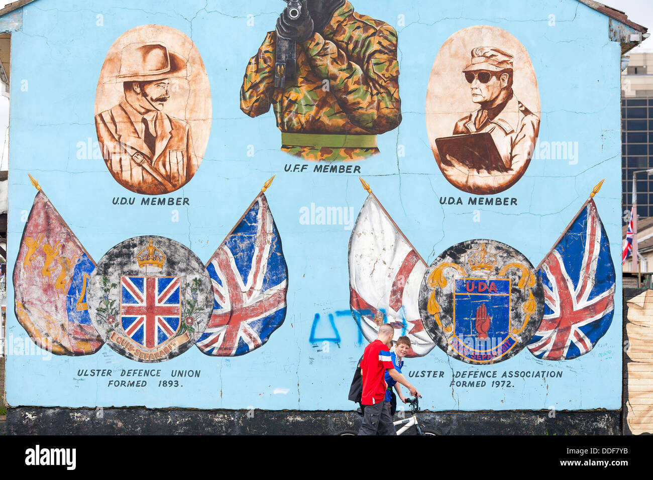 A political mural painted on a wall in Belfast, Northern Ireland depicts the sniper following the catholics on the - Stock Image