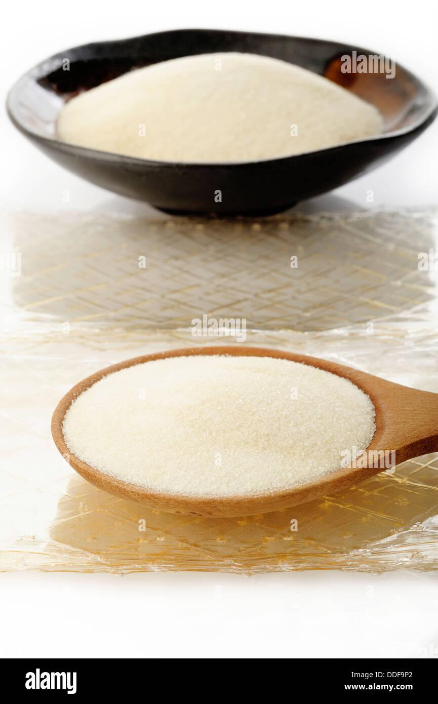 Gelatin Granules and Gelatin sheet on white - Stock Image