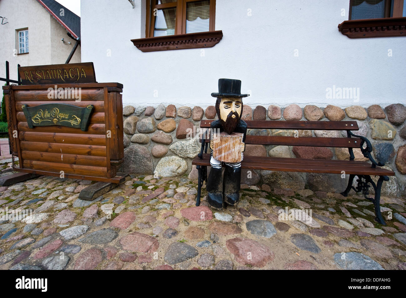 A wooden figure of a klezmer musician in front of a restaurant in Tykocin, in north-eastern Poland. - Stock Image
