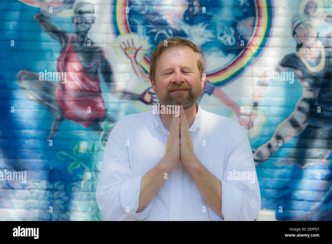 Man meditating infront of Center for the New Age Poster Sedona, Arizona - Stock Image