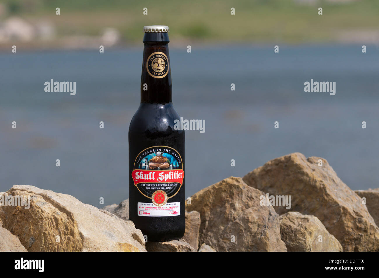 A bottle of the Orkney Brewery's Skull Splitter Rich Ale, in front of the Bay of First, Mainland, Orkney. Stock Photo