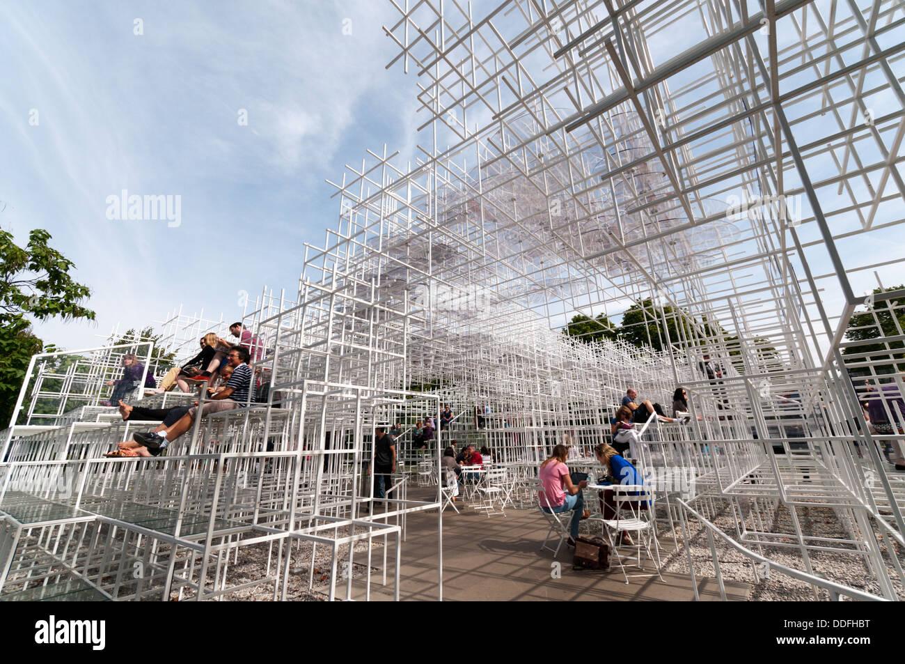 Visitors enjoying the 2013 Serpentine Gallery Summer Pavilion designed by the Japanese architect Sou Fujimoto. - Stock Image