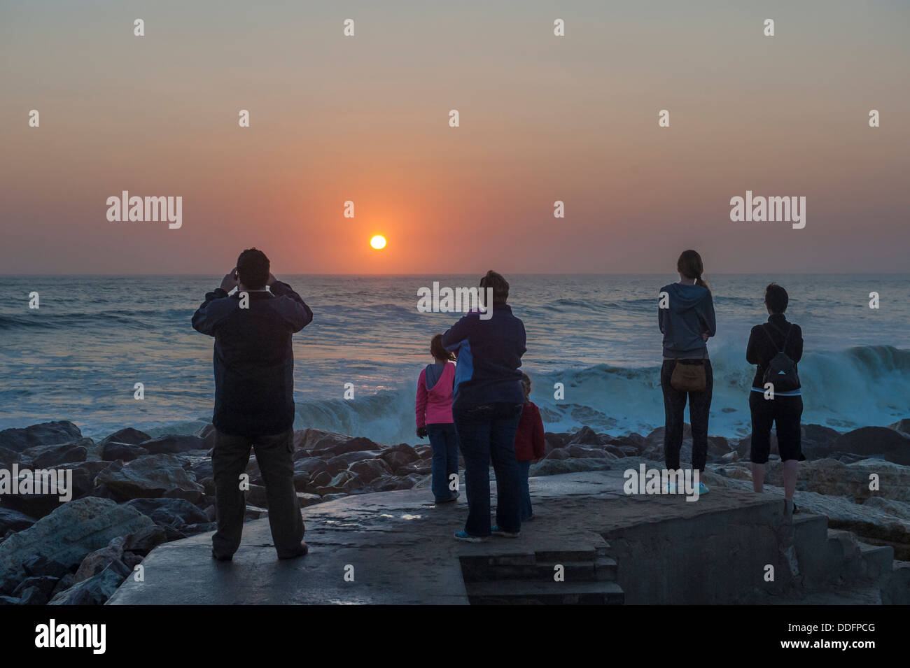 A family watches and photographs the  sunset over the ocean at Swakopmund, Namibia - Stock Image