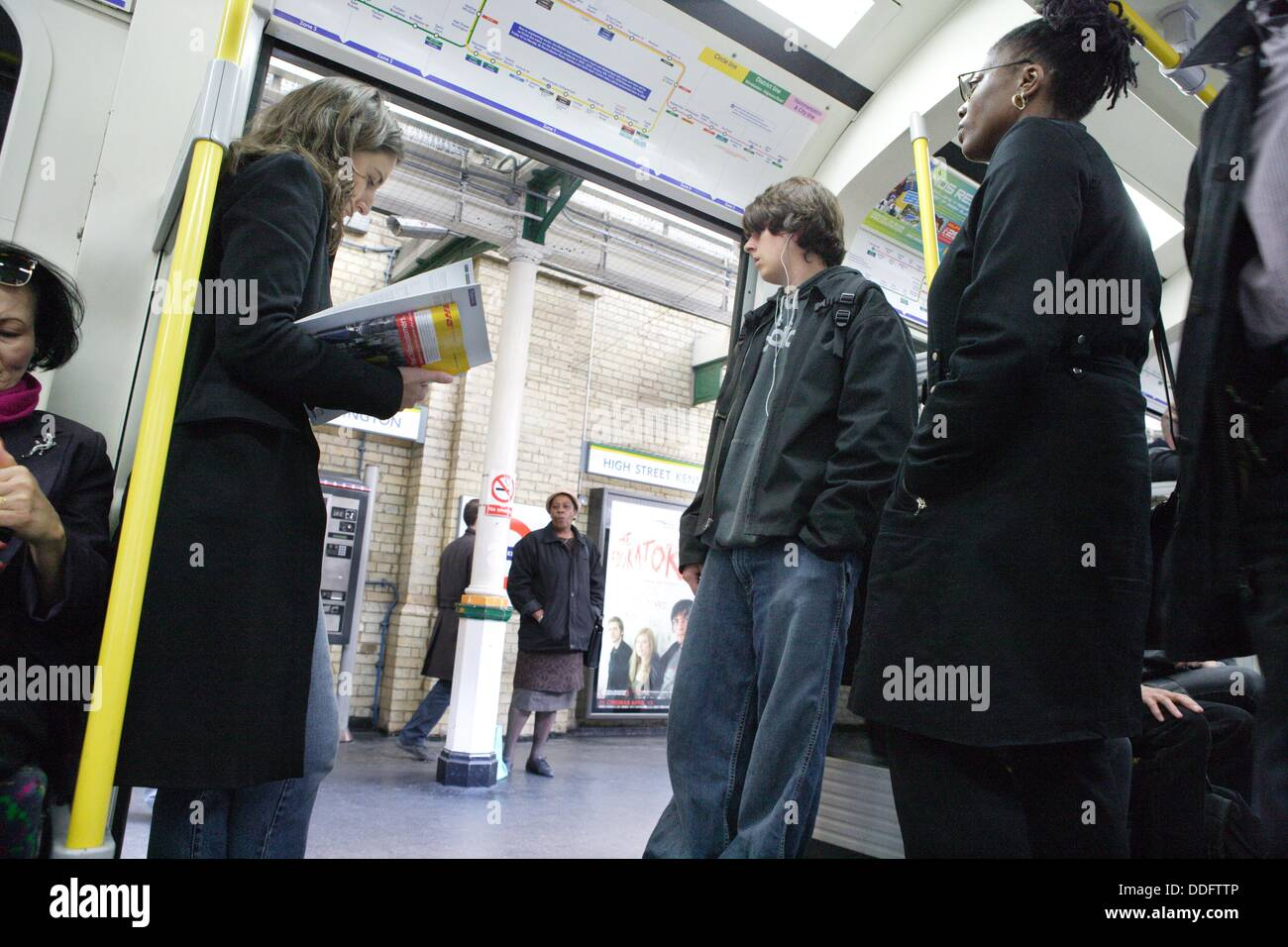 Tube train and commuters at a station, London, England - Stock Image