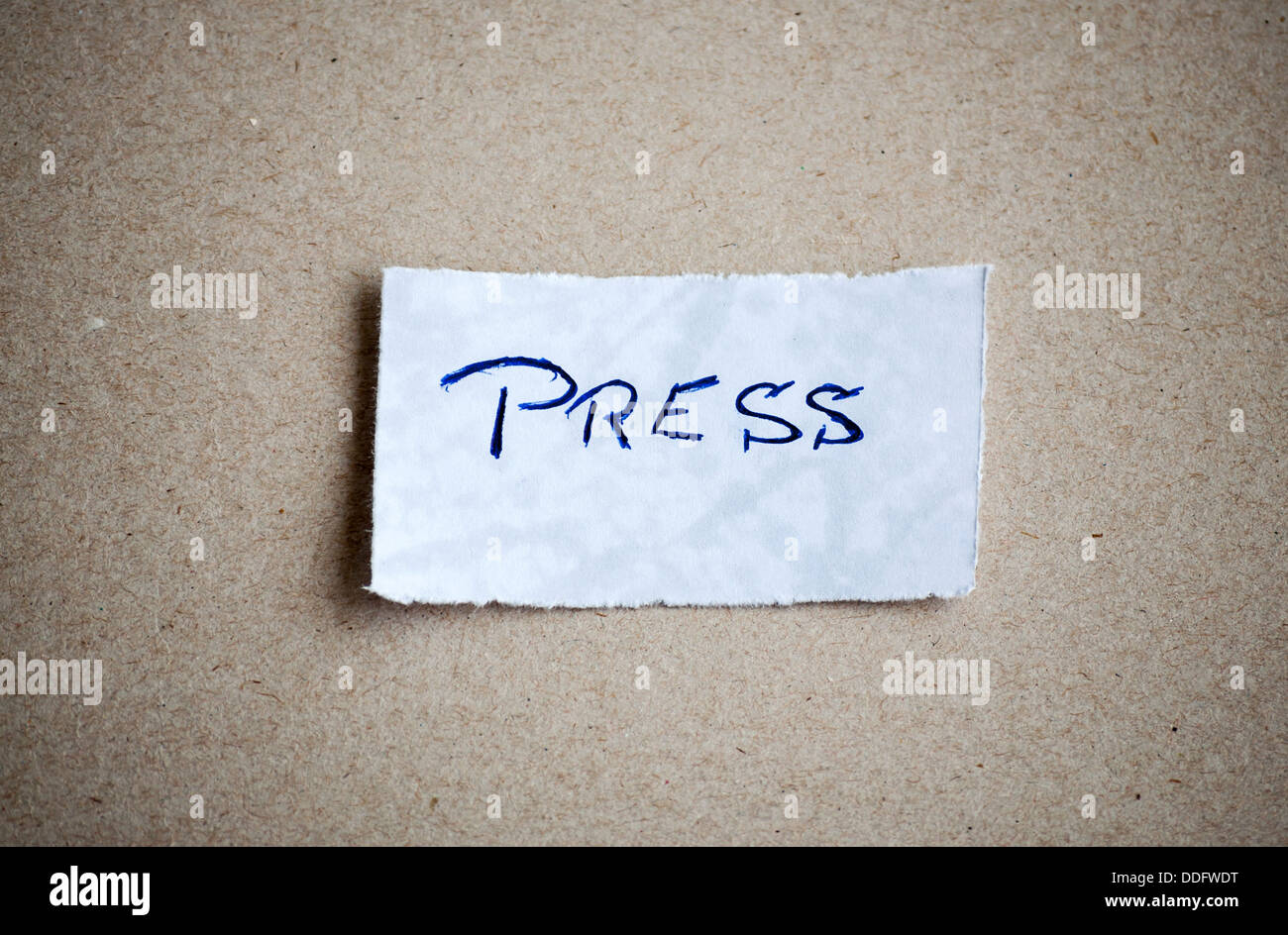 Press message,written on piece of paper, on cardboard background. Space for your text. - Stock Image