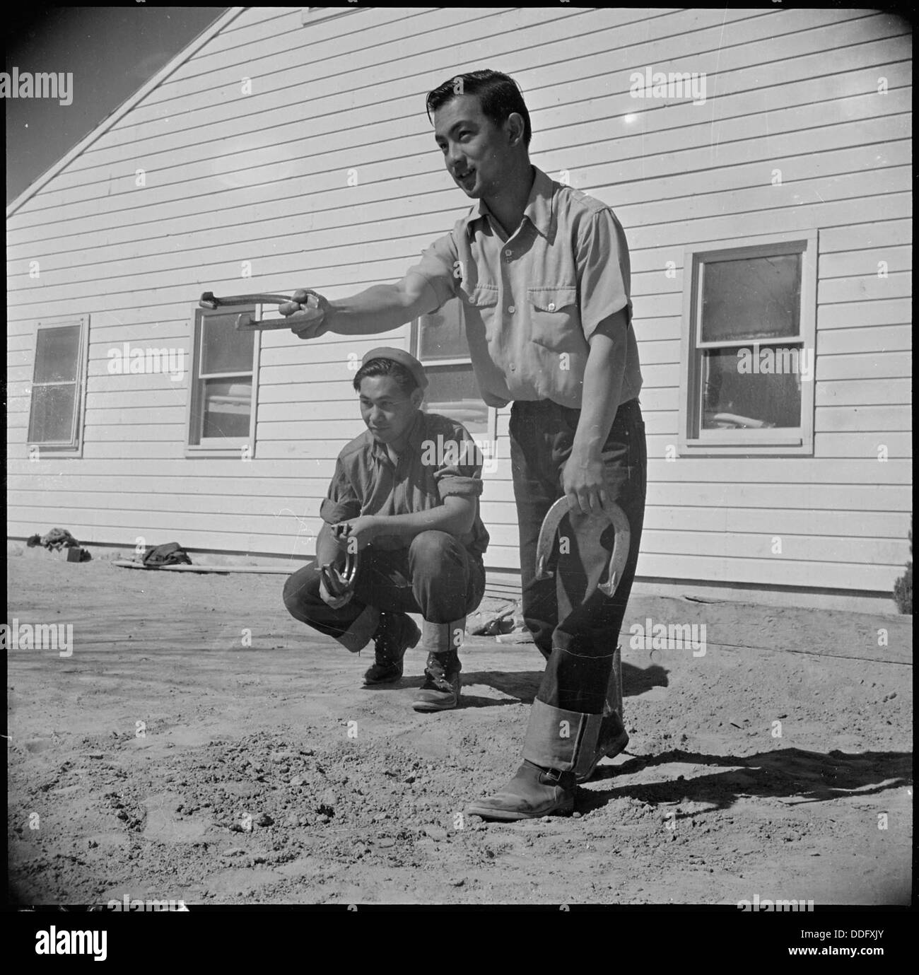 Topaz, Utah. Henry Yamashiro watches Tad Horita pitch a game of horseshoes. Members of this fire d . . . 537011 - Stock Image