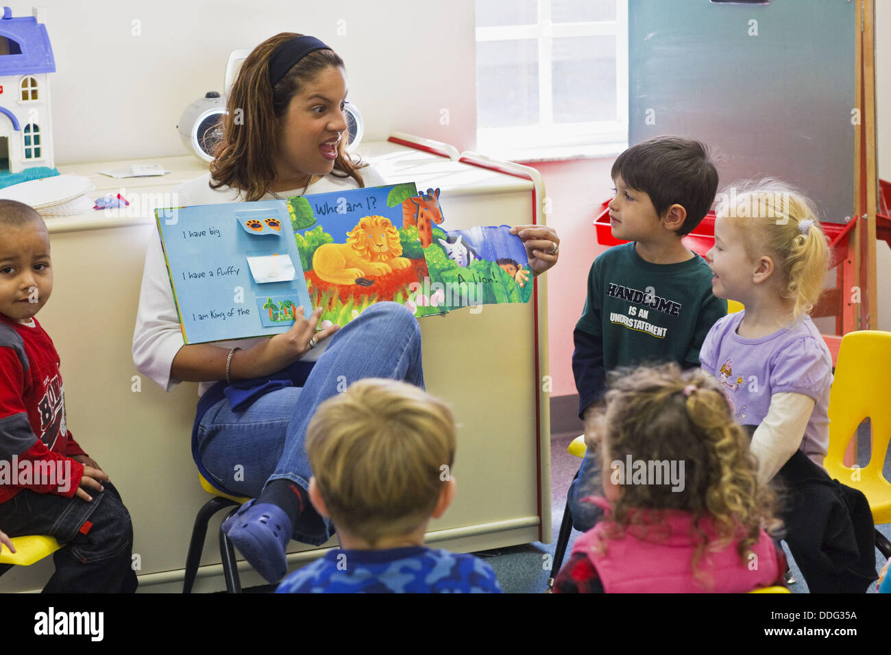 Hispanic Teacher Reading Book To Young Students In Preschool