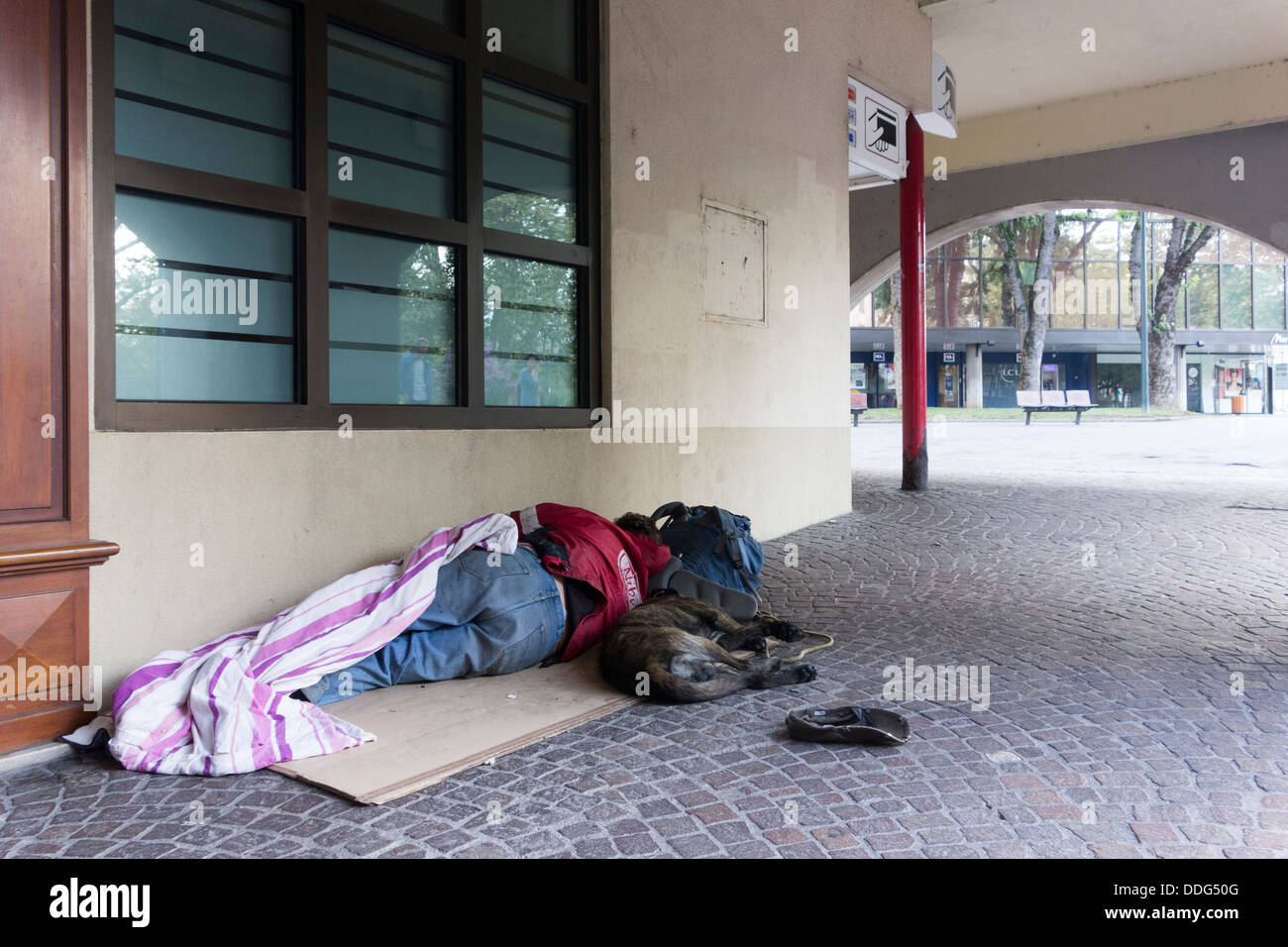 homeless man with dog sleeping on pavement, Annecy, France - Stock Image