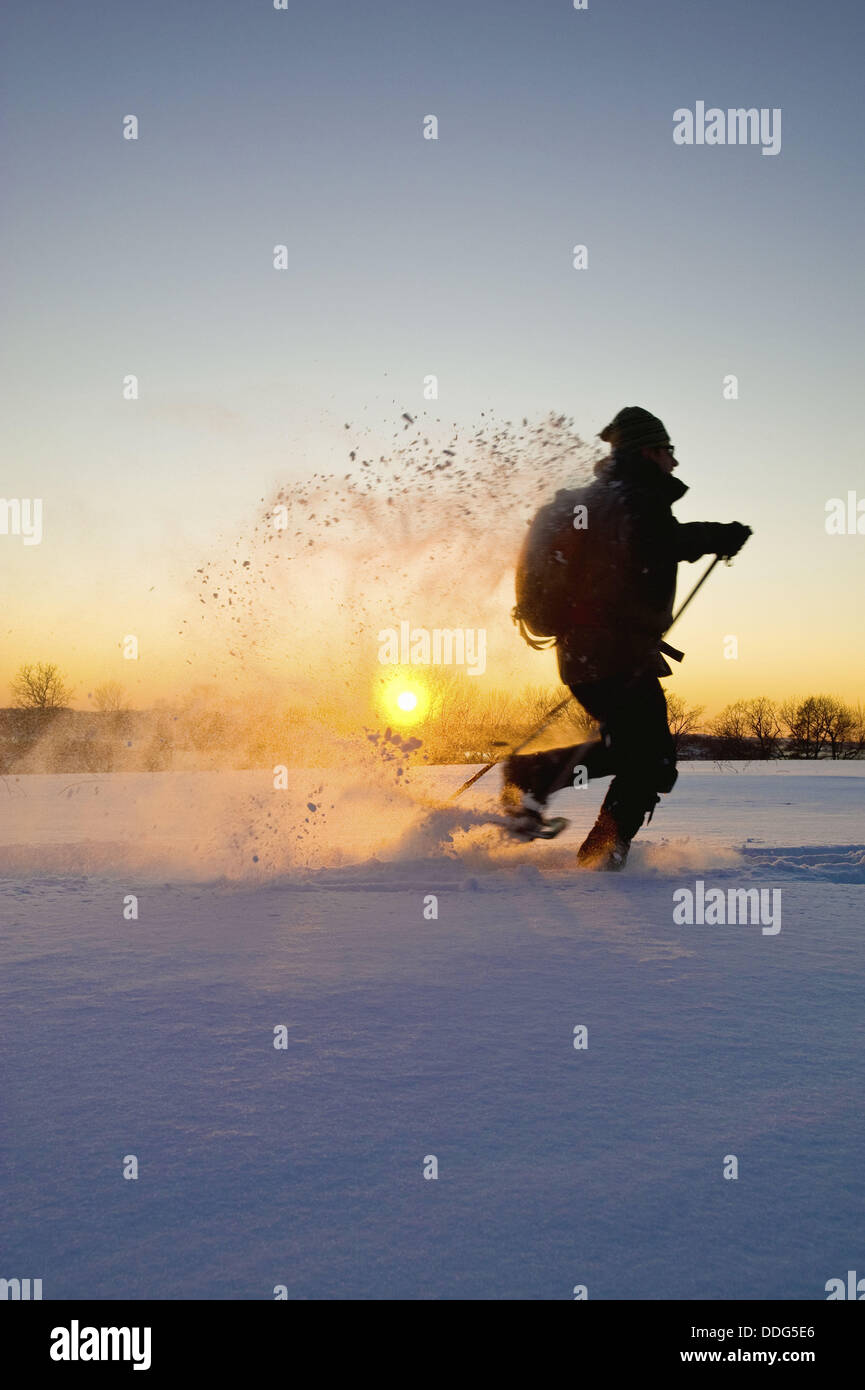 Silhouette of a man with backpack snowshoing as the sun sets on the horizon. Stock Photo