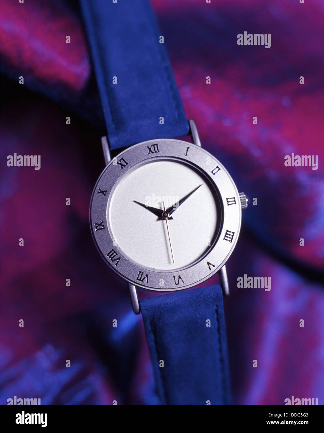 Watch with roman numeral on a purple silken background Stock Photo