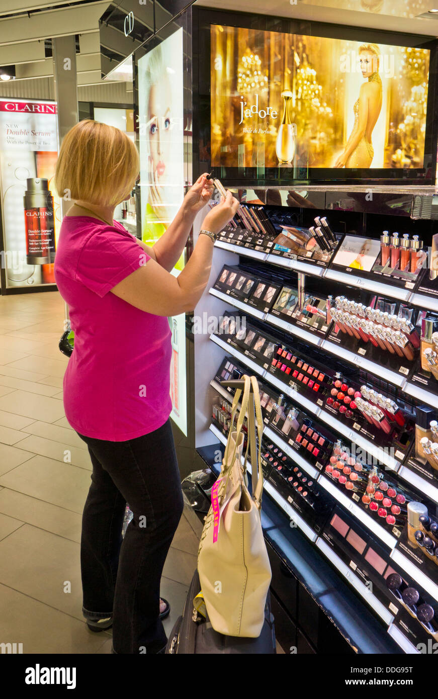 woman traveller shopping for duty free free cosmetics make up beauty products perfume in an airport duty free shop - Stock Image