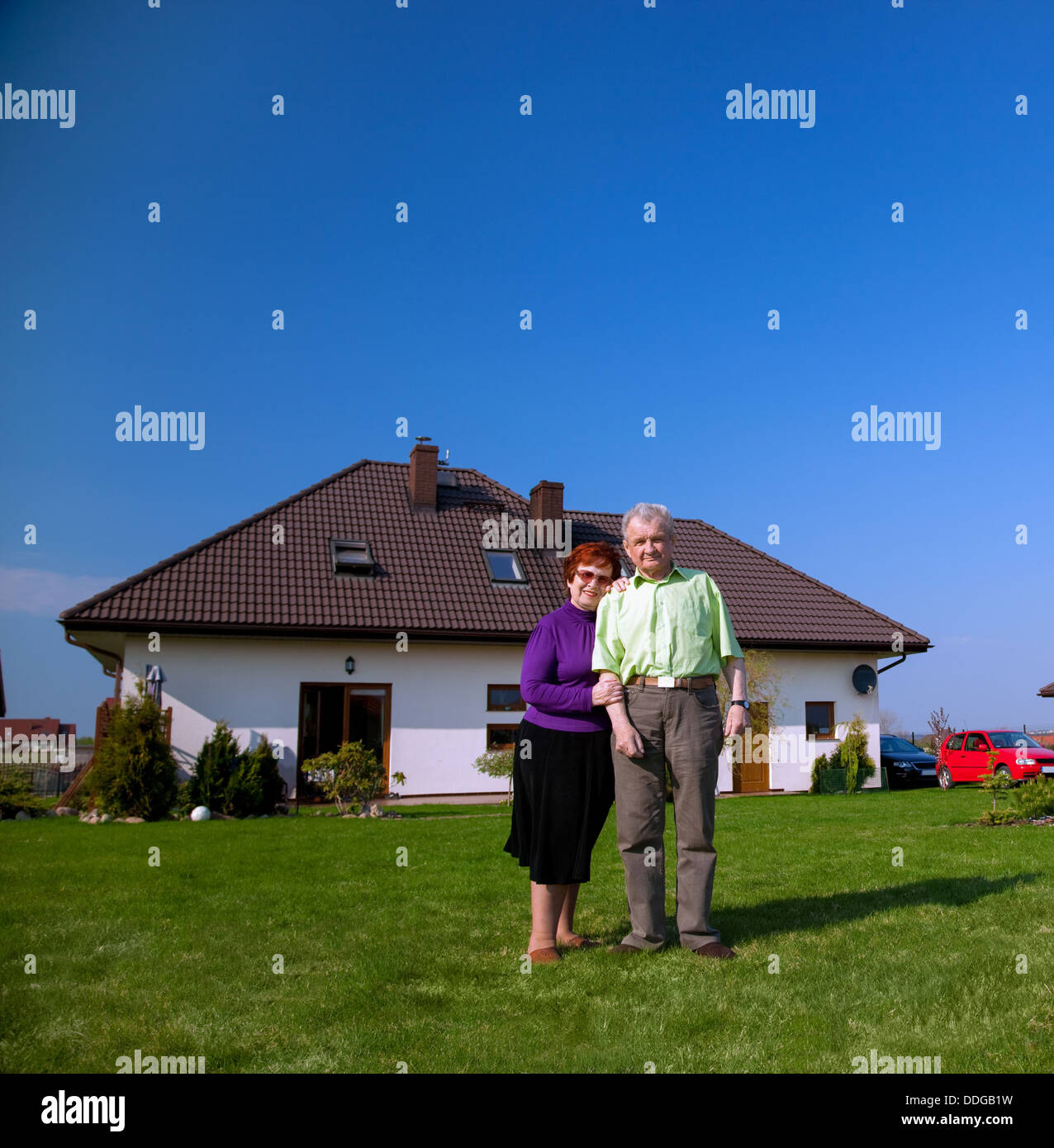 Senior smiling couple in the garden in front of their new house - Stock Image