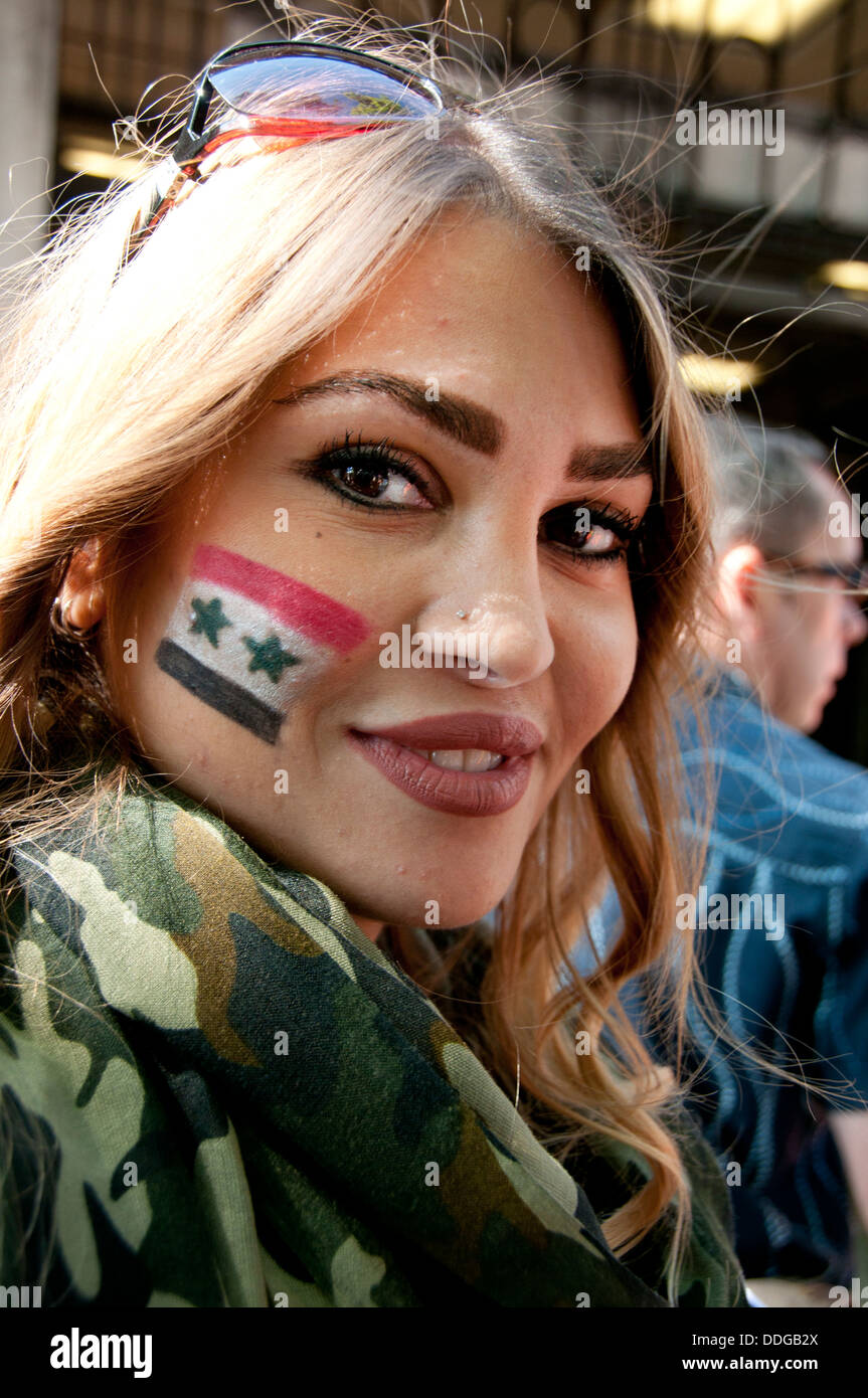 Demonstration against any intervention in Syria. A young blonde woman has a Syrian flag on her cheek and camouflage Stock Photo