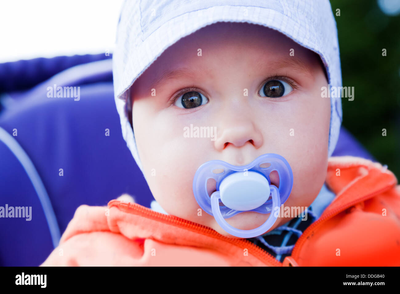Young baby boy with a dummy in his mouth outside in his push chair - Stock Image