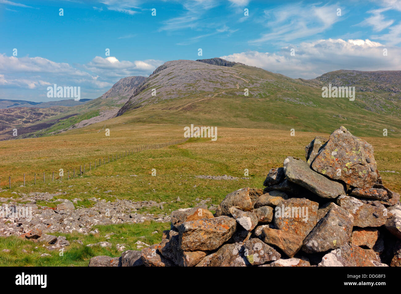 A view of Cader Idris, showing the pony path rising up to the summit, with a cairn of rocks in the near right foreground. - Stock Image