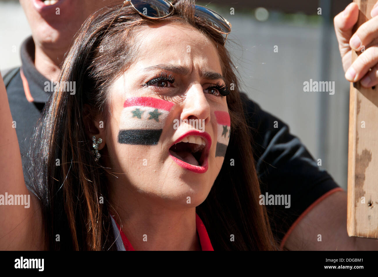 Young Syrian woman with flag painted on her cheek at demonstration against intervention in Syria Stock Photo