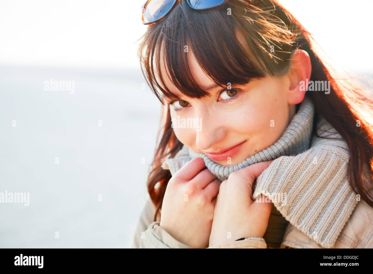 Portrait of a beautiful young woman standing by the sea on a sunny day in winter - Stock Image