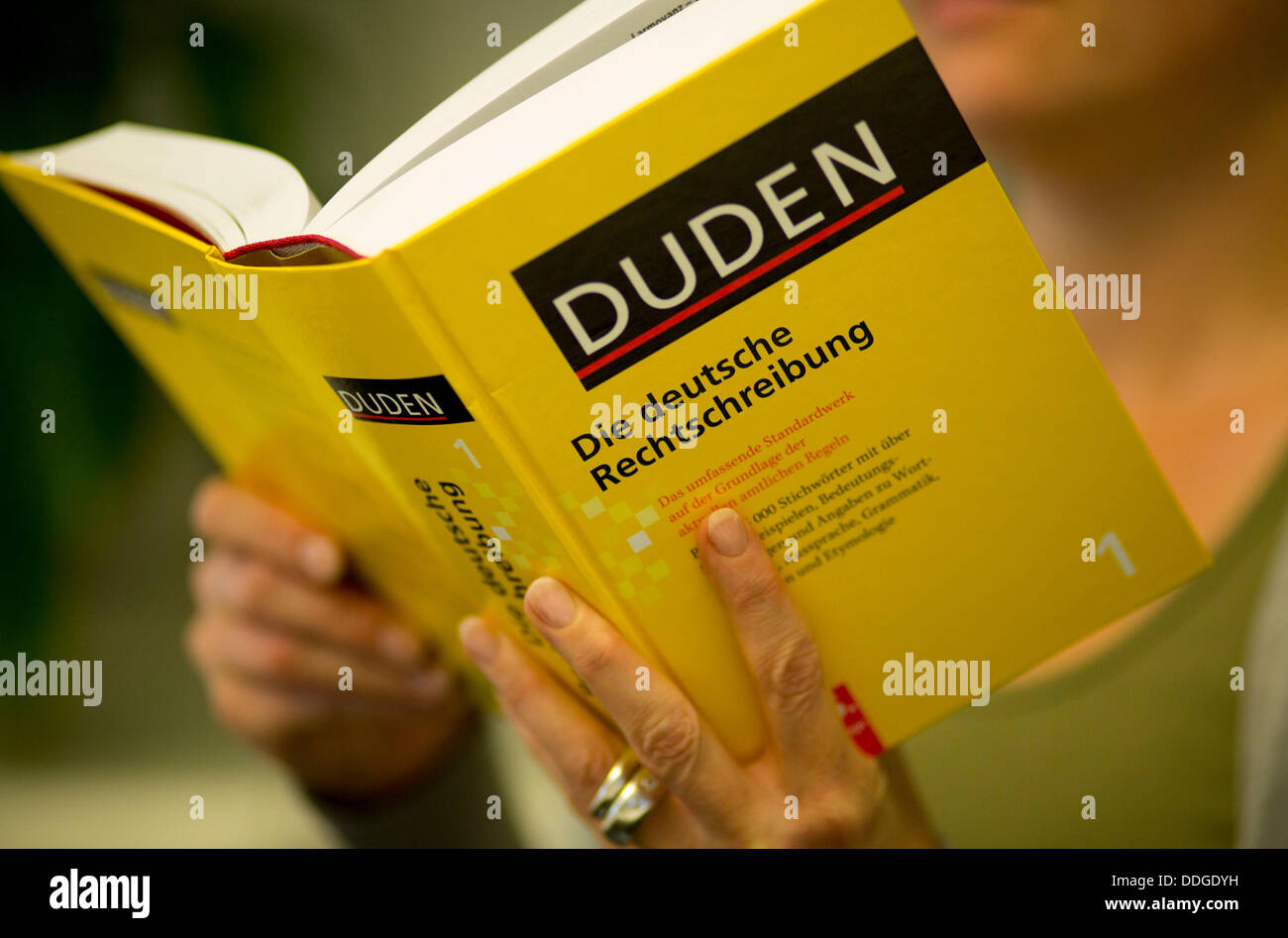 ILLUSTRATION - An illustrated picture shows a woman holding a Duden in her hands in Berlin, Germany, 02 September - Stock Image