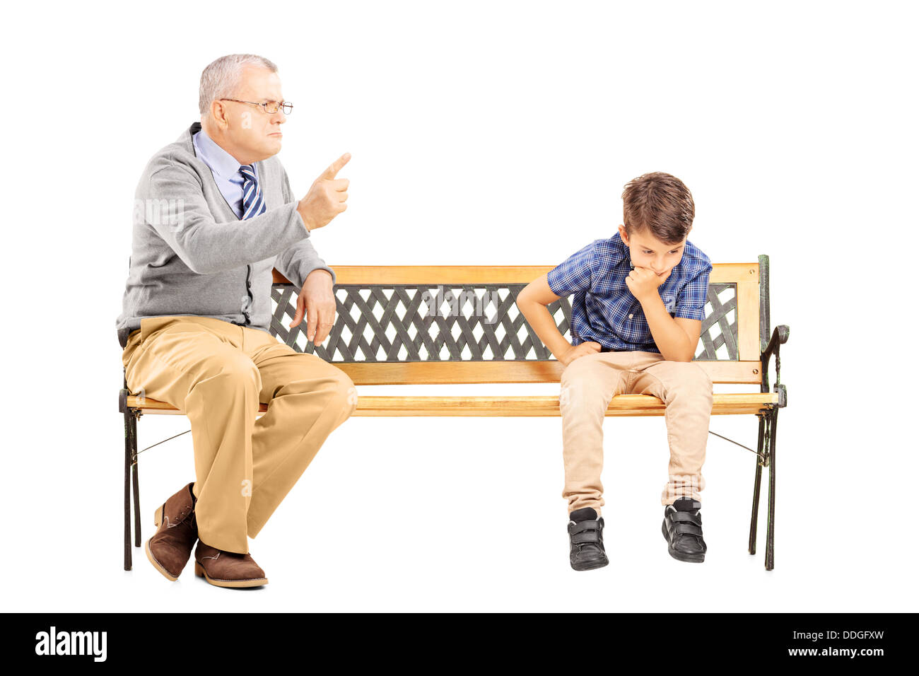 Angry grandfather shouting at his sad nephew, seated on a wooden bench - Stock Image
